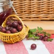 Basket with berries of a red gooseberry and jam - Stock Photo