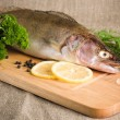 Stock Photo: Pike perch on a wooden kitchen board, it is isolated on white