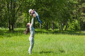 Mother raising her little child up high — Stock Photo