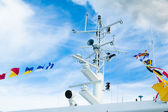 Mast with the navigating equipment of a yacht and alarm flags — Stock Photo