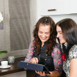 Stock Photo: Two young women friends chatting at home and using laptop to loo