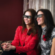 Stock Photo: Young beautiful women watching 3D TV at home