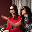 Young beautiful women at home watching a 3D movie — Stock Photo