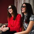 Stock Photo: Two beautiful women watching 3D TV at home