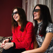 Two beautiful women watching 3D TV at home — Stock Photo