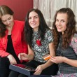 Three young beautiful women make purchases on the Internet at ho — Stockfoto