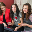 Three young beautiful women make purchases on the Internet at ho — Stock Photo