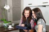 Two young women friends chatting at home and using laptop to loo — Stock Photo