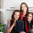 Three young women friends chatting at home and using laptop to l — Stock Photo
