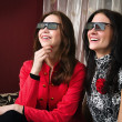 Young beautiful women watching 3D TV at home — Stockfoto