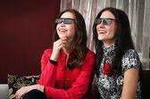 Young beautiful women watching 3D TV at home — Stock Photo
