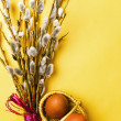 Bunch of willow branches and two Easter eggs in basket — Stock Photo