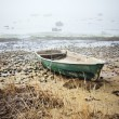 Old fishing boat at coast foggy in the morning — Stock Photo