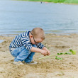 Boy and girl playing in the sand on the shore of Lake — Stock Photo