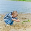 Boy and girl playing in the sand on the shore of Lake — Stock Photo #34394209