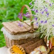 Buns in a wicker basket and a bouquet of field flowers — Stock Photo