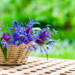 Stock Photo: Bunch of cornflowers in a wicker basket. Summer background