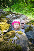 Young children, the boy with the girl hid among the rocks — Stock Photo