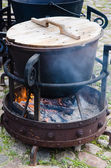 Old pot for cooking over a campfire, close-up. — Stock Photo