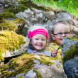 Stock Photo: Young children, boy with girl hid among rocks