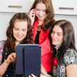 Three women friends chatting at home and using laptop to look at — Stock Photo