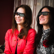 Two beautiful women at home watching a 3D movie — Stock Photo