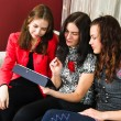 Three women friends chatting at home and using laptop to look at — Stock Photo #38622773