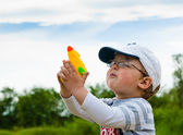 Little boy plays with a water pistol — Stock Photo