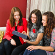 Three young women friends chatting at home and using laptop to l — Stock Photo #40135659