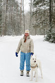 Woman with a dog on a walk in the woods during a snowfall — Stock Photo