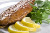 Smoked fish with lemon and salad — Stock Photo