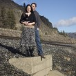 A young couple posing by train tracks — Stock Photo #19388069