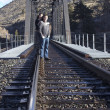Young couple in love on the train tracks — Stock Photo