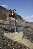 A young couple posing by train tracks — Stock Photo