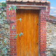Stock Photo: Wooden door in an old stone fence