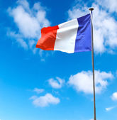 French flag on a background of blue sky — Stock Photo