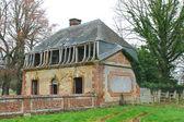 Opuštěné cihlový dům za plotem. — Stock fotografie