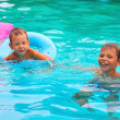 Two brothers are swimming in the pool — Stock Photo #27827397