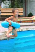 Joyful boy are jumping to the swimming pool — Stock Photo