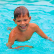 Smiling boy swims in pool on summer vacations — Stock Photo