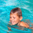 Smiling boy in the swimming pool on summer vacations — Stock Photo