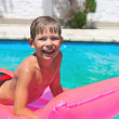 Smiling boy lies on pink mattress in the pool — Stock Photo