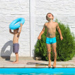 Two brothers near swimming pool at summer vacation — Stock Photo #28752835