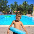 Stock Photo: Serious kid stands near the pool in the spa resort