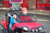 Two brothers are driving the red car — Stock Photo