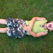 Stock Photo: Baby laughing, lying on the grass