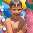 Smiling kid at a water park near the inflatable slides — Stock Photo