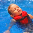 Tranquil kid in vest floating on her back at the pool aqua park — Foto Stock