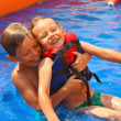 Two brothers in swimming pool at the water park — Stock Photo