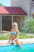 Güzel kız havuz kenarında bir yaz gününde oturur — Stok fotoğraf